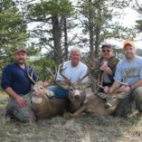 Four hunters and three whitetail bucks